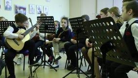 Los niños toman clases musicales Muchacho que toca la guitarra metrajes