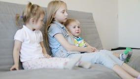 Los niños tristes se sientan en el sofá y el reloj TV metrajes
