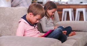 Los niños utilizan los dispositivos de Digitaces mientras que los padres hablan en fondo almacen de video