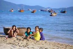 Los niños vietnamitas están jugando con la arena en la playa Foto de archivo libre de regalías
