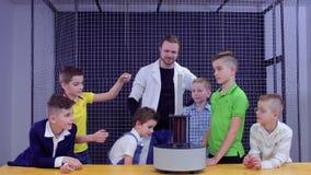 Los niños y el ayudante de laboratorio hace el experimento de la física en museo de ciencia metrajes