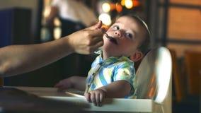Los niños y la comida, la madre da los alimentos para niños de una cuchara del bebé en un restaurante, el niño complace y rechaza metrajes