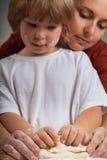 Los niños y la madre y amasan la pasta junta Imagen de archivo