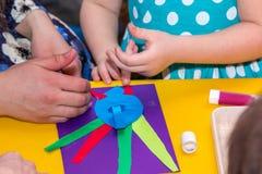 Los niños y las manos de los adultos pegan el documento coloreado sobre palo del uso Imagen de archivo libre de regalías