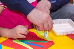 Los niños y las manos de los adultos pegan el documento coloreado sobre palo del uso Fotografía de archivo libre de regalías