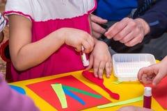 Los niños y las manos de los adultos pegan el documento coloreado sobre palo del uso Imágenes de archivo libres de regalías