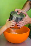 Los niños y las manos del papá tamizan la harina Foto de archivo