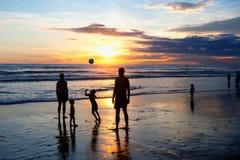 Los niños y los adultos juegan la bola en la playa durante puesta del sol Foto de archivo libre de regalías