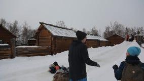Los niños y los adultos montan de la colina helada usando las cartulinas almacen de metraje de vídeo