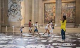 Los niños y los turistas gozan del JR caras en el piso del panteón de París Fotografía de archivo libre de regalías
