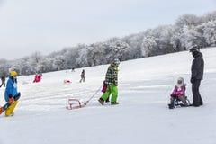 Los niños y sus padres sledding en el lado de la montaña Imagen de archivo libre de regalías