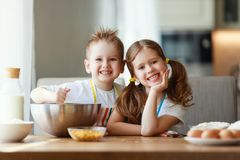 Los ni?os divertidos de la familia feliz cuecen las galletas en cocina imagenes de archivo