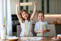 Los ni?os divertidos de la familia feliz cuecen las galletas en cocina fotografía de archivo libre de regalías