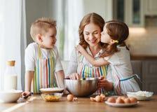 Los ni?os divertidos de la familia feliz cuecen las galletas en cocina foto de archivo
