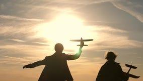 los ni?os juegan el aeroplano del juguete Los adolescentes quieren hacer piloto y astronauta Las muchachas felices corren con el  metrajes