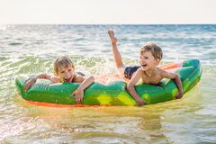 Los ni?os nadan en el mar en un colch?n inflable y divertirse imagen de archivo libre de regalías