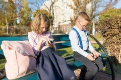 Los ni?os serios elegantes muchacho y muchacha est?n mirando en smartphones En un banco con las mochilas de la escuela fotos de archivo
