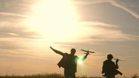 Los ni?os son maldicen en el fondo del sol con un aeroplano a disposici?n Dos muchachas juegan con el avi?n del juguete en la pue almacen de video