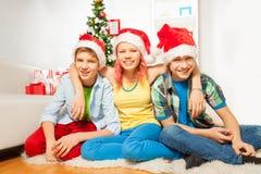 Los niños de las adolescencias en Año Nuevo van de fiesta en los sombreros de Papá Noel Fotos de archivo libres de regalías