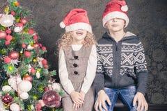 Los niños divertidos en el día de fiesta de la Navidad cerca adornaron el árbol de navidad Imágenes de archivo libres de regalías