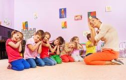 Los niños en el grupo juegan al juego que finge dormir Imágenes de archivo libres de regalías