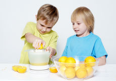 Los niños exprimen hacia fuera el zumo de naranja Foto de archivo libre de regalías