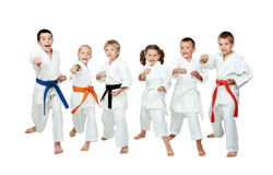 Los niños jovenes en kimono realizan karate de las técnicas en un fondo blanco Fotos de archivo