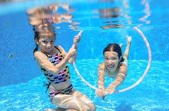 Los niños nadan en la piscina subacuática, las muchachas activas felices se divierten debajo del agua, deporte de los niños Imagen de archivo