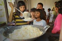 Los niños privados consiguen el alimento en el tiempo del almuerzo Imágenes de archivo libres de regalías