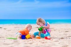 Los niños que construyen una arena se escudan en una playa Foto de archivo libre de regalías
