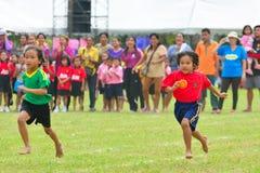 Los niños que hacen un trabajo en equipo corren la carrera en el día del deporte de la guardería Fotografía de archivo