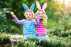 Los niños que juegan con el busket de los huevos en el huevo de Pascua cazan Fotos de archivo