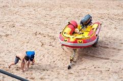 Los niños que juegan en la playa cerca de un bote de salvamento de la resaca en Umhlanga oscilan Fotos de archivo libres de regalías
