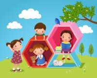 Los niños que jugaban y que leían con hexágono formaron en la yarda Fotos de archivo