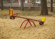 Los niños seesaw en patio arenoso en parque de la ciudad Foto de archivo libre de regalías