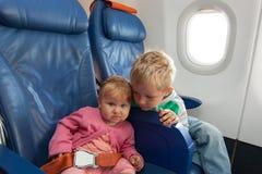 Los niños viajan en avión - niño pequeño y niña pequeña en vuelo Fotografía de archivo libre de regalías
