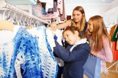 Los niños y su madre buscan la ropa en tienda Foto de archivo
