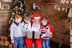 Los novios divertidos previenen a Santa Claus de los regalos que ordenan en l Fotografía de archivo