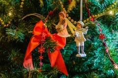 Los nuevos juguetes del ` s del sí cuelgan en un árbol de navidad contra el contexto de la guirnalda que brilla intensamente Fotografía de archivo