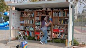 Los nuevos libros se están colocando en la biblioteca de la calle en Israel metrajes