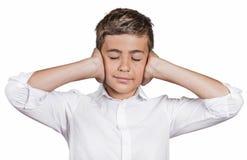 Los oídos de la cubierta del muchacho con las manos, no quieren oír el fuerte ruido, ignorando la conversación Fotografía de archivo libre de regalías