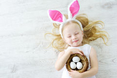 Los oídos del conejito de la niña que llevan linda que juegan el huevo cazan en Pascua Foto de archivo libre de regalías