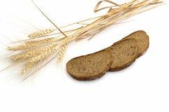 Los oídos del trigo y de tres pedazos de pan que son i presentado Foto de archivo libre de regalías