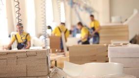 Los obreros de los muebles en guardapolvos amarillos recogen los muebles, fabricación de los muebles, interior industrial, pequeñ almacen de metraje de vídeo