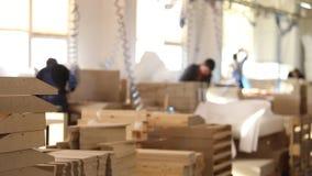 Los obreros de los muebles en guardapolvos amarillos recogen los muebles, fabricación de los muebles, interior industrial, pequeñ almacen de video