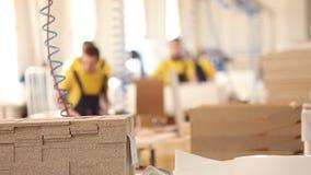 Los obreros de los muebles en guardapolvos amarillos recogen los muebles, fabricación de los muebles, interior industrial, pequeñ metrajes