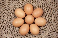 Los ocho huevos del pollo en fondo de mimbre Imágenes de archivo libres de regalías
