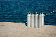 Los ocho tanques del equipo de submarinismo que se colocan en el embarcadero al lado del agua fotografía de archivo