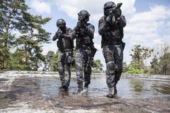 Los oficiales de policía de los ops de espec. GOLPEAN CON FUERZA en el agua Imágenes de archivo libres de regalías