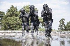 Los oficiales de policía de los ops de espec. GOLPEAN CON FUERZA en el agua imagen de archivo libre de regalías